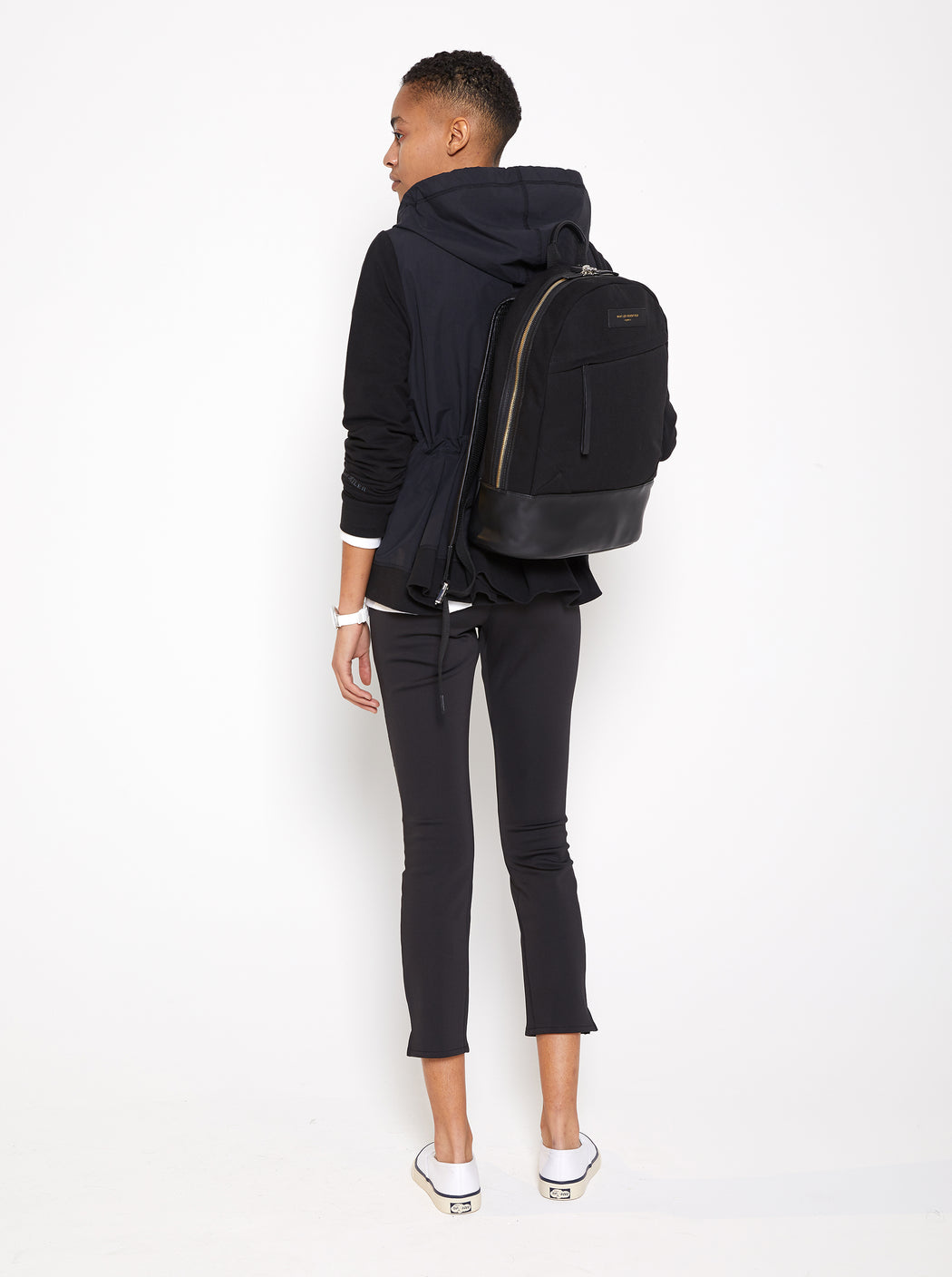 Model wearing Women Back Pleated Hoodie Zip-Up made with Organic Cotton in Black (Back View)