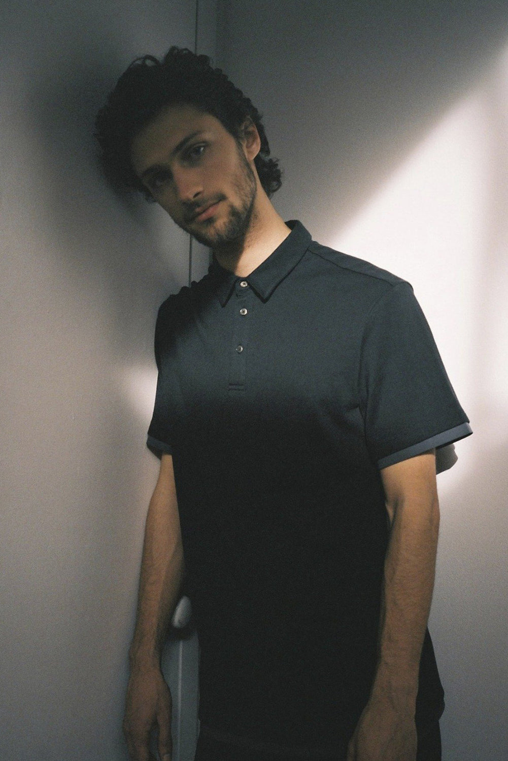 Model wearing Men Contrast Polo Shirt, made with Organic Cotton in Black (Front view)