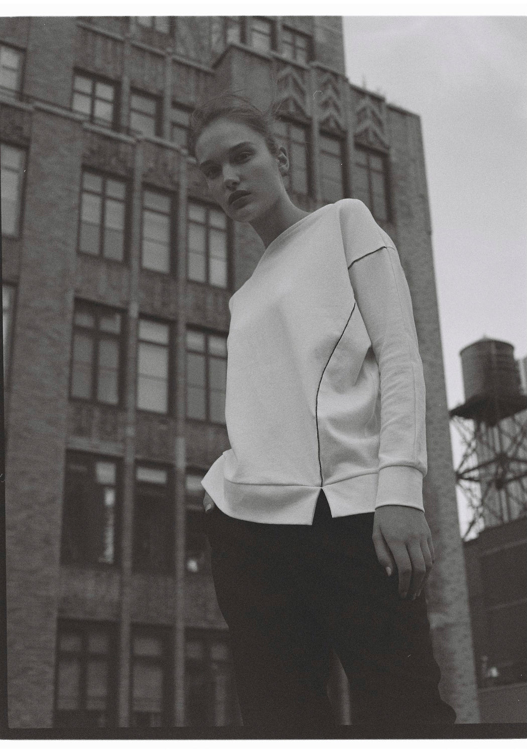 Model wearing women Long Sleeve T-Shirt, Asymmetric hem beading detail made with Organic Cotton in White (side view)