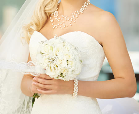 Woman wearing a wedding dress and pearls
