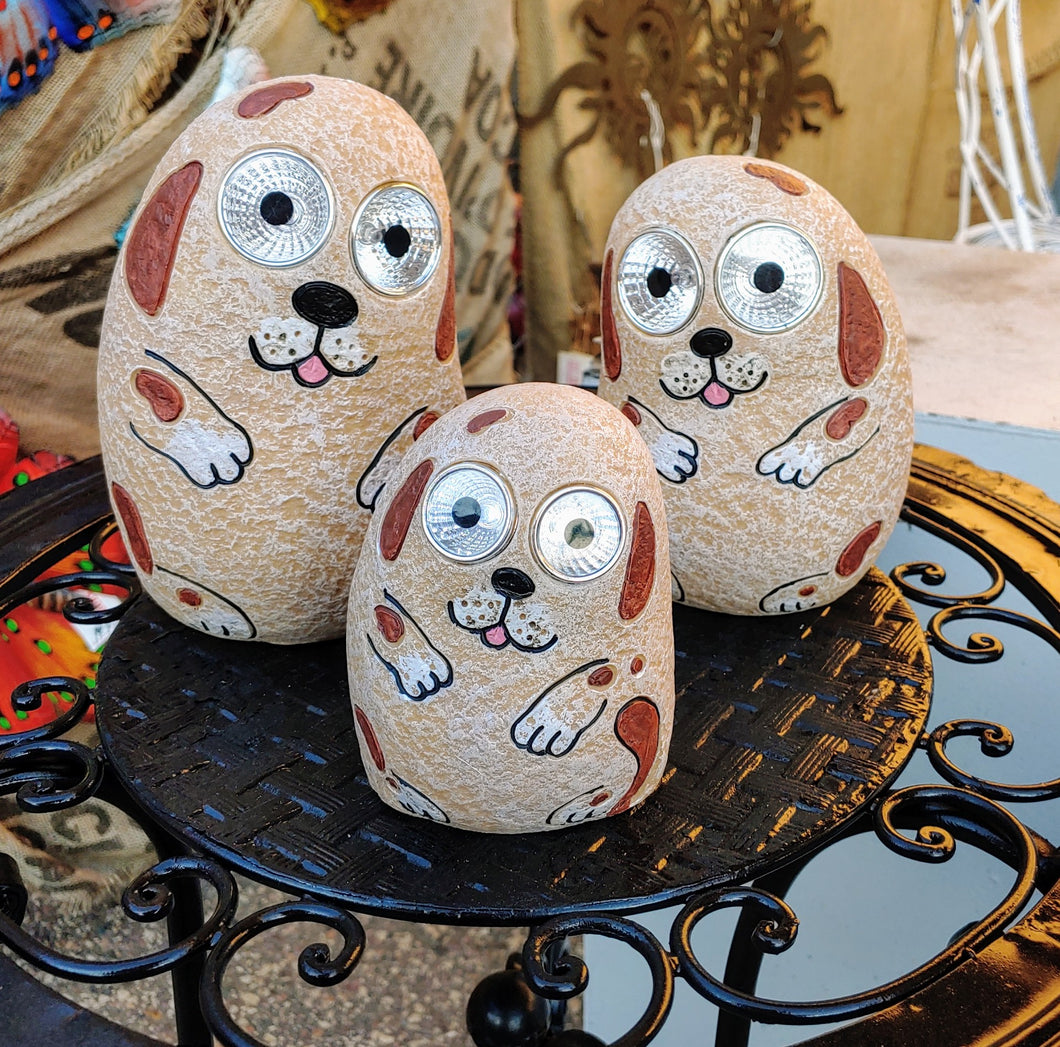 SOLAR-POWERED, CERAMIC DOG FAMILY GROUP HAS 6 INCH, 5 INCH, AND 4 INCH TALL ANIMALS. THEY ARE SITTING ON A ROUND, METAL STAND. THEIR BODYS ARE LIGHT TAN WITH BROWN, FLOPPY EARS, AND SPOTS. THEY HAVE A HAPPY FACE DESIGN. CLEAR GLASS EYES LIGHT UP.
