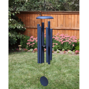 AN IODIZED, DARK BLUE, ALUMINUM WINDCHIME/WINDCATCHER. IT IS HANGING OVER A GRASS YARD. IT HAS 6 ALUMINUM POWDERCOATED TUBES, LARGE TOPPER, AND WINDCATCHER DOWN THE MIDDLE. BEHIND ARE TREES, A LARGE MUSHROOM STATUE UNDER A TREE, AND A FLOWER GARDEN ALONG A WOODEN PRIVACY FENCE.