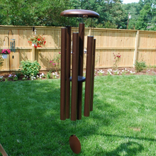Load image into Gallery viewer, AN IODIZED, BRONZE, ALUMINUM WINDCHIME/WINDCATCHER. IT IS HANGING FROM A PLANT HANGER OVER A GRASS YARD. IT HAS 6 ALUMINUM POWDERCOATED TUBES, LARGE TOPPER, AND WINDCATCHER DOWN THE MIDDLE. BEHIND ARE TREES, POWERLINES, A SECOND WINDCHIME HANGING WITH A PLANT FROM A PLANT HANGER, AND A FLOWER GARDEN ALONG A WOODEN PRIVACY FENCE.