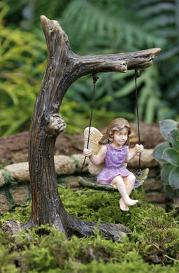 little girl fairy sitting on a tree swing wearing a purple sleeveless dress.  The seat she is sitting on is a leave.  The tree appears to be an old dead tree with the perfect branch for a swing.