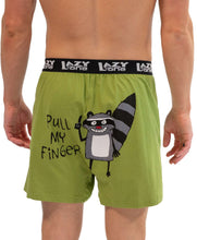 "Load image into Gallery viewer, BACK VIEW OF MAN WEARING UNI-SEX BOXERS (PAJAMA BOTTOMS) | LIME-GREEN WITH BLACK, EXPOSED ELASTIC BAND 'LAZY ONE' | 100% COMBED-COTTON KNIT | NO-FADE PRINT/NO SEAMS TO INTERFERE WITH GRAPHIC – SMILING, BLACK, GREY, AND WHITE RACCOON/LEFT INDEX FINGER UP | WORDS IN BLACK: ""PULL MY FINGER."" SIZES: M, L, XL."