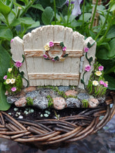 Load image into Gallery viewer, FAIRY GARDEN – RESIN – 'HINGED GATE' | MG376 | GATE WORKS, OVER GREY, TAN, WHITE, STONE PATH WITH MOSS | CLOSED, FLORAL WREATH/PINK AND YELLOW FLOWERS; SAME ON THE BLOOMS AND FLOWERING VINE AT GATE POST BASES. WOVEN BASKET, PURPLE/WHITE FLOWERS, BRIGHT GREEN LEAVES.