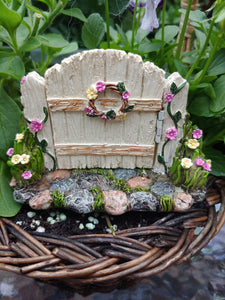 FAIRY GARDEN – RESIN – 'HINGED GATE' | MG376 | GATE WORKS, OVER GREY, TAN, WHITE, STONE PATH WITH MOSS | CLOSED, FLORAL WREATH/PINK AND YELLOW FLOWERS; SAME ON THE BLOOMS AND FLOWERING VINE AT GATE POST BASES. WOVEN BASKET, PURPLE/WHITE FLOWERS, BRIGHT GREEN LEAVES.
