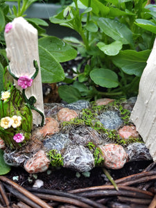 FAIRY GARDEN – RESIN – 'HINGED GATE' | MG376 | GATE WORKS, OVER GREY, TAN, WHITE, STONE PATH WITH MOSS | FULLY OPENED, PINK AND YELLOW FLOWERS ON THE BLOOMS AND FLOWERING VINE AT GATE POST BASE. WOVEN BASKET, PURPLE/WHITE FLOWERS, BRIGHT GREEN LEAVES.