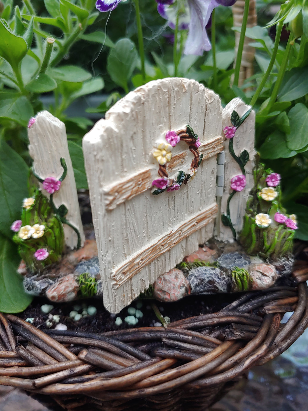 FAIRY GARDEN – RESIN – 'HINGED GATE' | MG376 | GATE WORKS, OVER GREY, TAN, WHITE, STONE PATH WITH MOSS | PARTIALLY OPENED, FLORAL WREATH/PINK AND YELLOW FLOWERS; SAME ON THE BLOOMS AND FLOWERING VINE AT GATE POST BASES. WOVEN BASKET, PURPLE/WHITE FLOWERS, BRIGHT GREEN LEAVES.