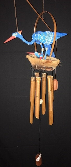 A BAMBOO AND COCONUT WINDCHIME. HAS A BLUE STORK STANDING OVER 2 BLUE, BOBBLE-HEAD BABIES. THEY ARE IN THE COCONUT SHELL. THERE ARE 6 HANGING BAMBOO CHIMES UNDER THE COCONUT WITH A WINDCATCHER IN THE MIDDLE.