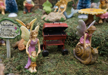 Load image into Gallery viewer, FAIRY IN A PINK DRESS KNEELING ON A BROWN SNAIL|3 INCHES TALL. THEY ARE IN THE FAIRY GARDEN WITH FAIRY MOM IN A PURPLE DRESS WALKING FAIRY BOY IN A GREEN SHIRT AND BROWN SHORTS|RED GRILL|SIGN 'WELCOME TO MY GARDEN'.