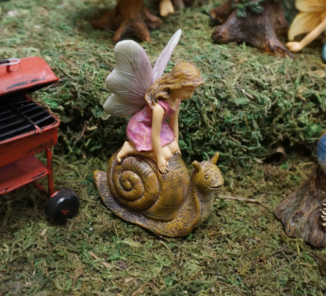FAIRY IN A PINK DRESS KNEELING ON A BROWN SNAIL|3 INCHES TALL. THEY ARE IN THE FAIRY GARDEN.