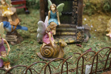 Load image into Gallery viewer, FAIRY IN A PINK DRESS KNEELING ON A BROWN SNAIL|3 INCHES TALL|HAS IRON FENCE IN FRONT. THEY ARE IN THE FAIRY GARDEN WITH FAIRY IN BLUE DRESS SITTING ON WATER FOUNTAIN STONES.