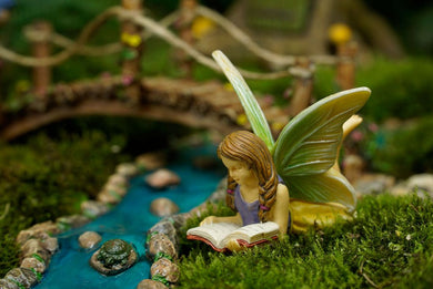 Fairy laying down reading a book