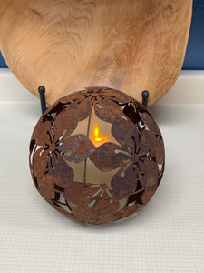 RUSTY METAL, 8 INCH ORB WITH A HIBISCUS FLOWER PATTERN OVER A LIT VOLTIVE CANDLE. IT IS SITTING IN FRONT OF A CARVED, WOODEN BOWL ON A WHITE TABLE.