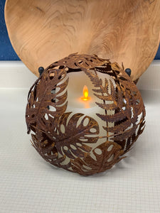 RUSTY METAL, 8 INCH ORB WITH A FERN LEAF PATTERN OVER A LIT VOLTIVE CANDLE. IT IS SITTING IN FRONT OF A CARVED, WOODEN BOWL ON A WHITE TABLE.
