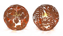 Load image into Gallery viewer, 2 RUSTY METAL, 8 INCH ORBS. THE LEFT ONE HAS A HIBISCUS FLOWER PATTERN WHILE THE RIGHT ONE HAS A FERN LEAF PATTERN.