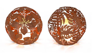 2 RUSTY METAL, 8 INCH ORBS. THE LEFT ONE HAS A HIBISCUS FLOWER PATTERN WHILE THE RIGHT ONE HAS A FERN LEAF PATTERN.