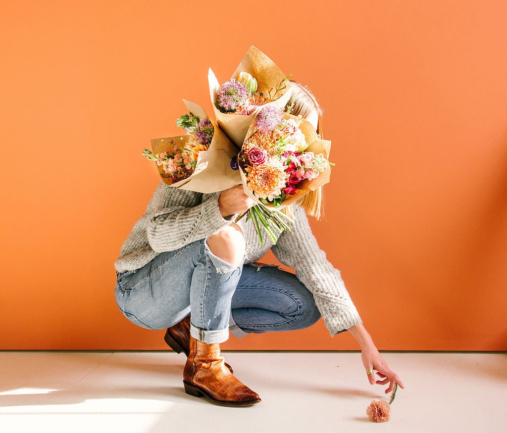 girl holding flower bouquets kneeling down to pickup flower in front of orange wall