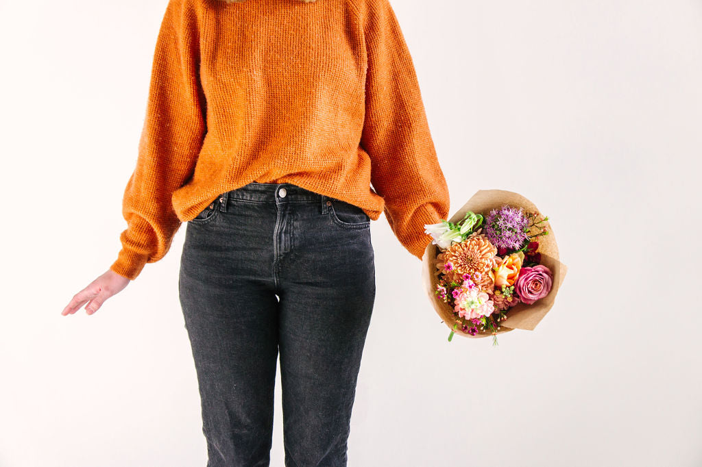 girl in orange sweater and black jeans holding flower bouquet