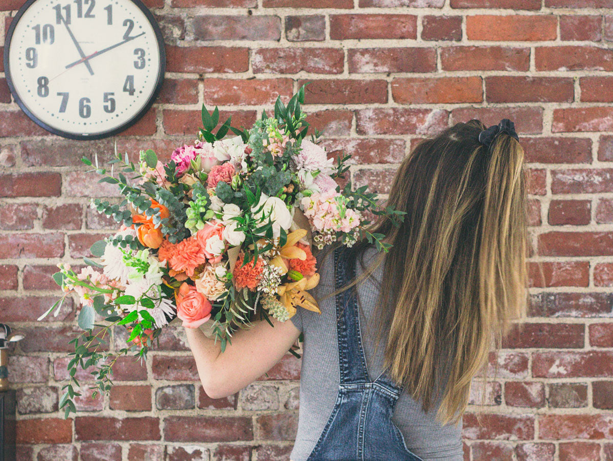 girl holding armful of flowers from wild valentine flower subscription service in new hampshire