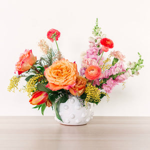 large flower arrangement with orange pink and yellow flowers on table