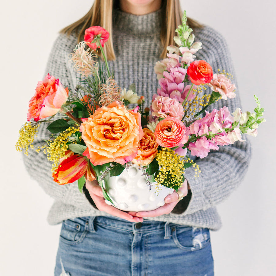 large flower arrangement with orange pink and yellow flowers held by girl in gray sweater