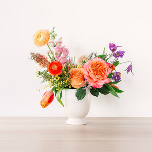 medium flower arrangement with orange pink and yellow flowers on table