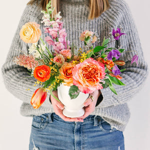medium flower arrangement with orange pink and yellow flowers held by girl in gray sweater
