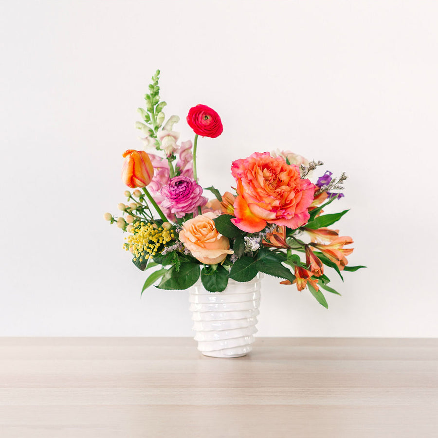small flower arrangement with orange pink and yellow flowers on table