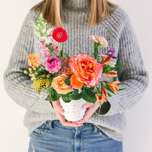 small flower arrangement with orange pink and yellow flowers held by girl in gray sweater