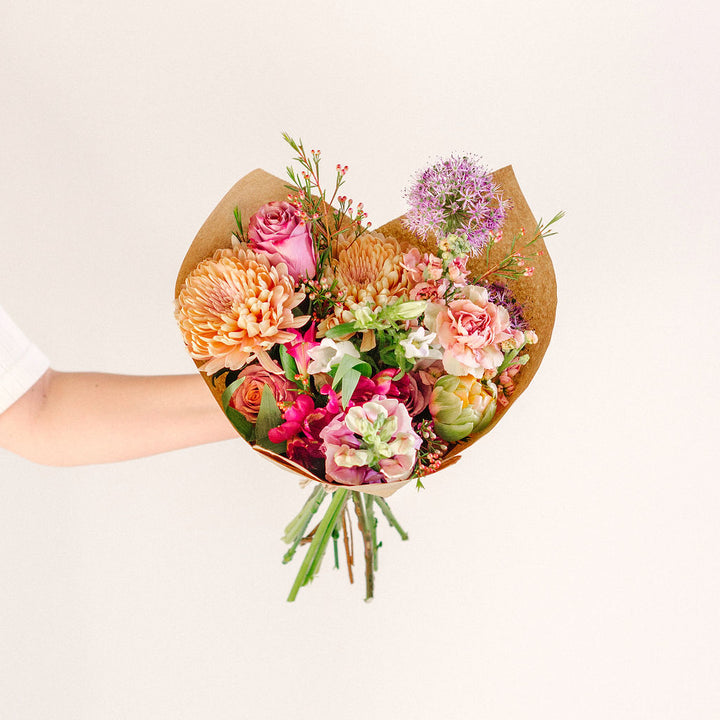 large flower bouquet in outstretched hand with pink orange and purple wildflowers