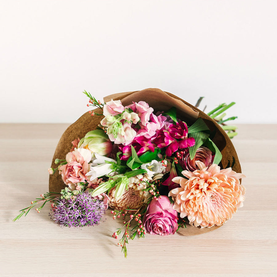 large flower bouquet laying on table with pink orange and purple wildflowers