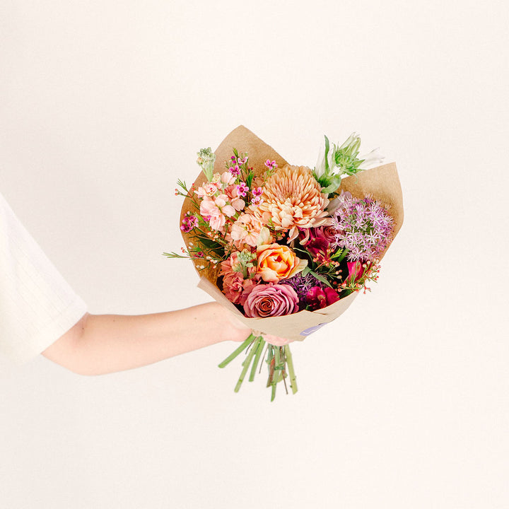 medium flower bouquet in outstretched hand with pink orange and purple wildflowers