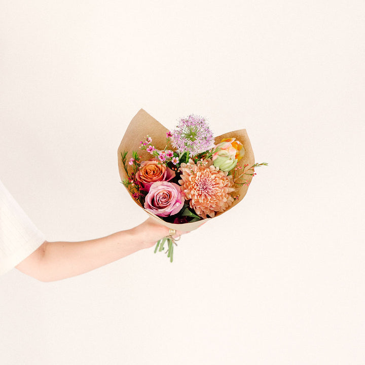 small flower bouquet in outstretched hand with pink orange and purple wildflowers