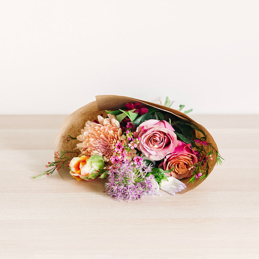 small flower bouquet laying on table with pink orange and purple wildflowers