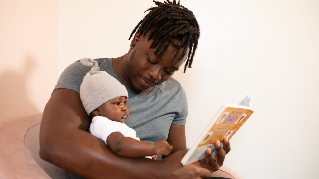 Dad reading to newborn baby