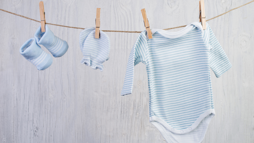 Onesie and baby clothing on clothesline