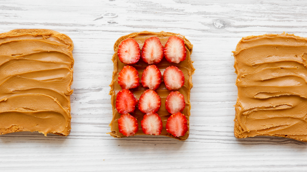 Peanut butter and strawberries on toast on white wooden table