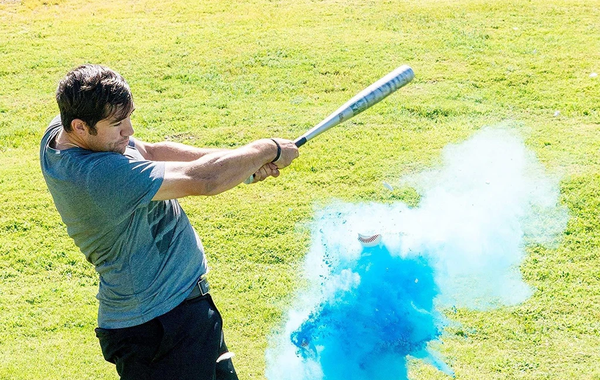 gender reveal party, hitting a blue smoke bomb with a baseball bat, it's a boy!