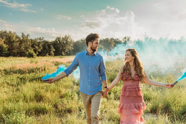 Expectant couple holding blue smoke cannons for gender reveal party