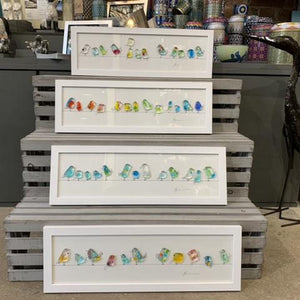 Fused glass birdies in multicoloures gathered on a wire, a charming piece available in a white or grey frame included