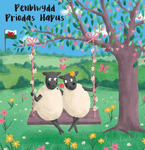 Penblwydd priodas hapus greetings card with two sheep cuddling on a swing in a flowery meadow.