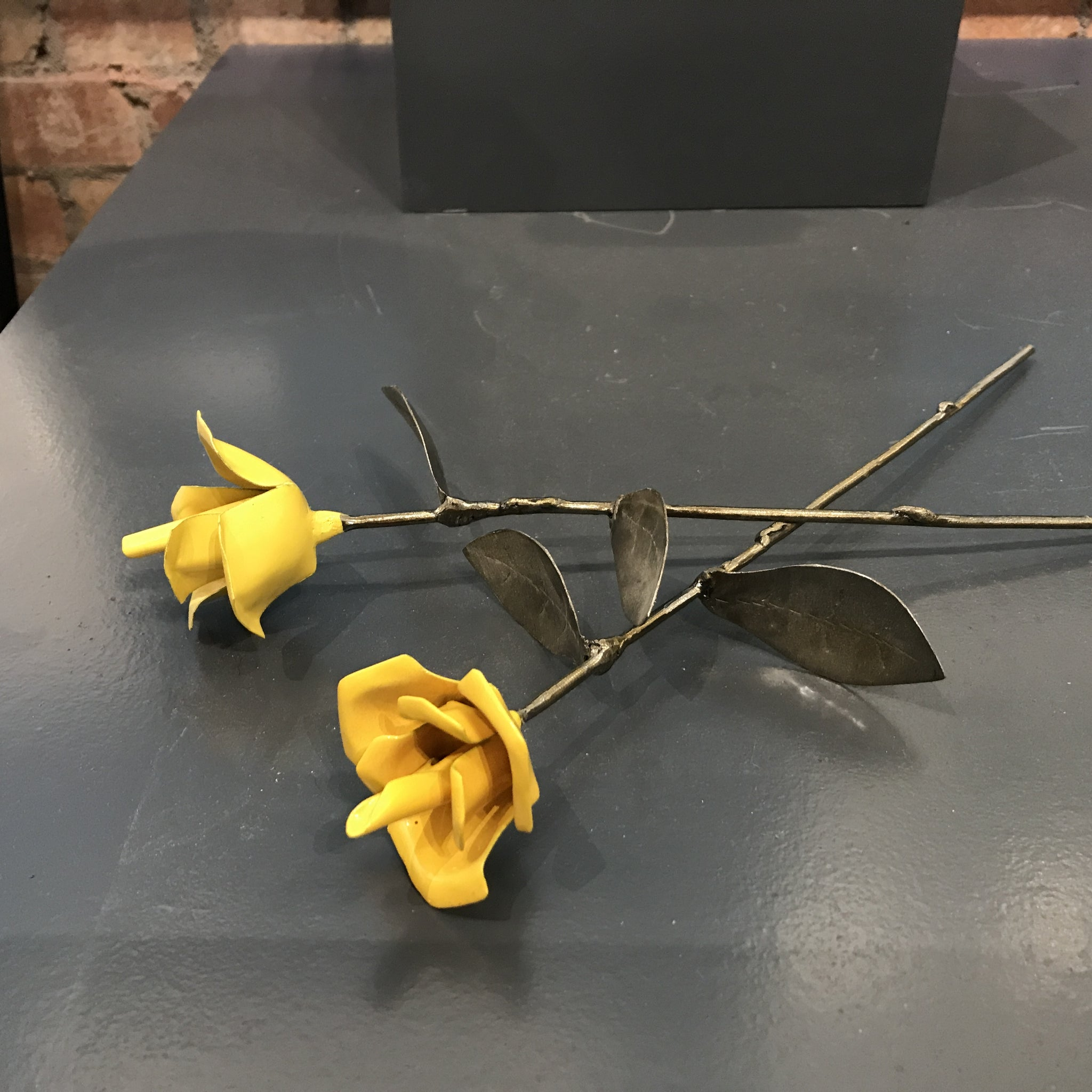 Yellow metal rose sold on behalf of Les Brooks