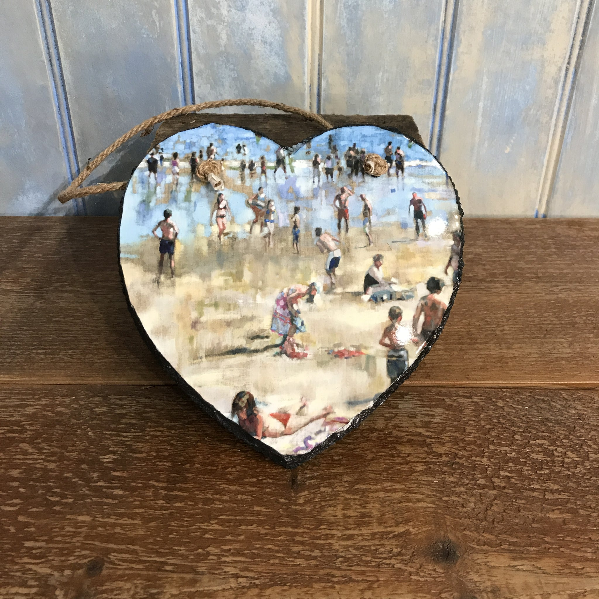 A slate heart printed with a beach scene from the painting Bank Holiday Langland by Arwen Banning