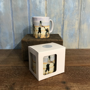 Ceramic mug illustrated with the painting Across the Beach of a family walking behind their mother who is pushing a pram across the sand and the sea in the distance. The convoy is followed by the pet dog. One mug is shown in a gift box.