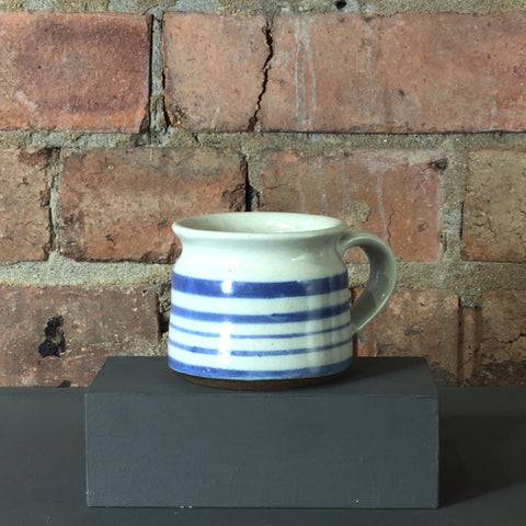 blue and white striped mug with a curved shaped rim.