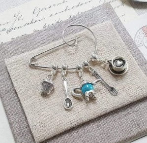 Charm brooch with silver teacup, teaspoon, cup cake and teal coloured teapot.