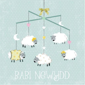 Babi Newydd greetings card with an illustration of five cartoon sheep hanging from a baby mobile.