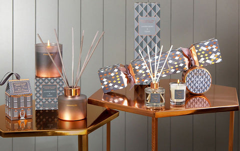 Gold side tables adorned in scented candles, diffusers and Christmas crackers.